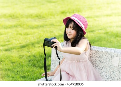 Little asian cute girl holding camera in hand and take a picture with selfie shot in park