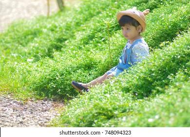 A little Asian cute girl is relaxing in the flower garden at Chiangmai,Thailand