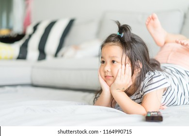 Little asian cute girl watching tv on her sofa alone.
