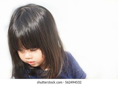 Little asian girl angry and sad looking down on white background.