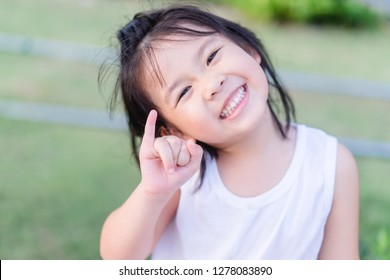 Little asian girl with big smile and try to reconciled sign or promise sign to her friend.