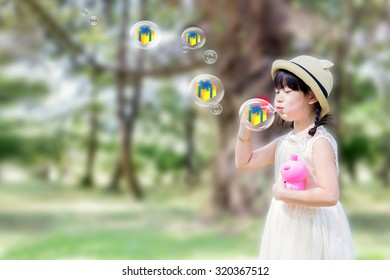 Little asian girl blowing soap bubbles. give box in the bubbles.