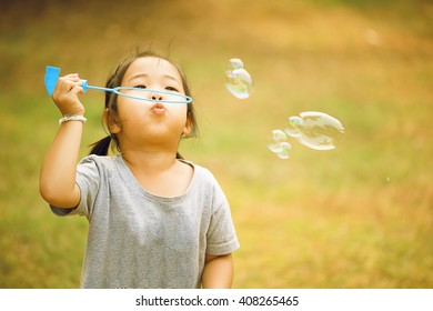 A little asian girl blowing soap bubbles, closeup portrait beautiful curly baby