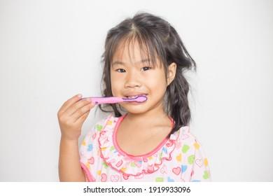 Little asian girl brushing her teeth in bathroom self brush teeth