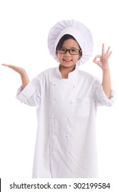 Little asian girl in chef uniform showing empty open hand palm