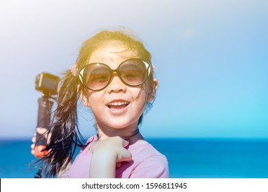 Little asian girl child holding action camera and recording video at the sea beach with sun light flare.Photographer kid girl smiling and happy when she take a photo with action cam video in vacation.