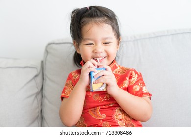 Little asian girl in chinese tradition dress drinking a carton of milk from a box with a straw,Cute little girl drinks milk using a drinking straw