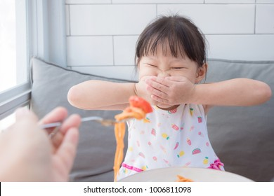 Little asian girl close her mouth by hands,refuse to eat tomato in spagethi from her mother.Picky eater child concept.