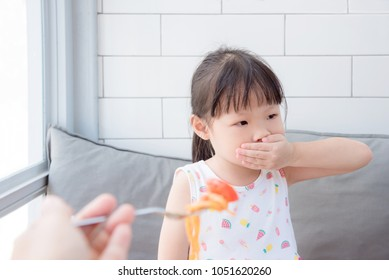 Little asian girl close her mouth by hand refuse to eat tomato in spaghetti from her mother
