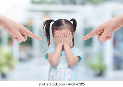 Little asian girl close her face by hands and crying while parents scold her at home.