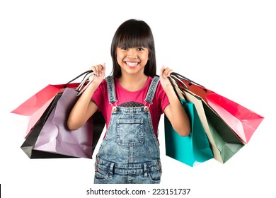 Little asian girl with colorful shopping bags, Isolated over white