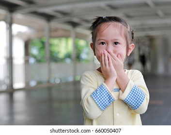 Little asian girl covering her mouth and nose with her hands.