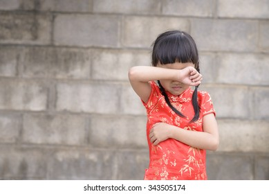 Little asian girl cry; Kid on red chinese dress with wall background