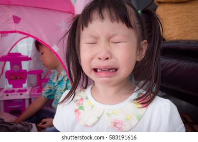 Little asian girl crying because a boy playing her toy