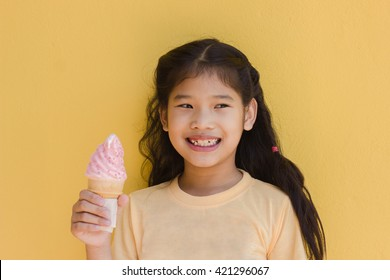 little Asian girl dressed in yellow eating ice cream on yellow wall background