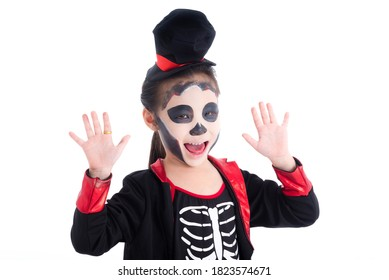 Little asian girl dressing skeleton haloween costume with face painting over white background.