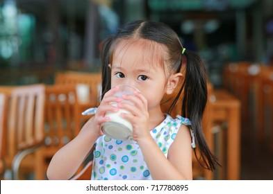 Little asian girl drinking milk in restaurant at the morning.