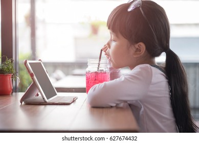 Little asian girl drinking red water in breakfast time. See the iPad