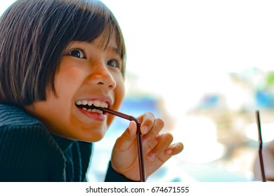 Little Asian girl drinking water from straw , lifestyle and people concept.