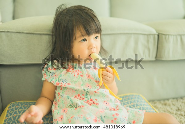 Swell Little Asian Girl Eating Banana On Stock Photo Edit Now Gmtry Best Dining Table And Chair Ideas Images Gmtryco