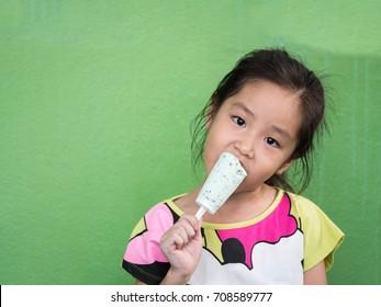 Little Asian girl eating ice cream, in summer