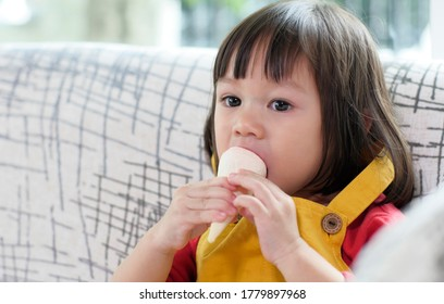 little Asian girl eating icecream in crispy cone.