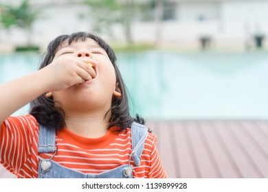 Little asian girl Eating snack with hands near swimming pool.Enjoy eating and hungry concept.