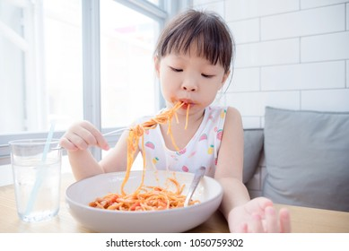 Little asian girl eating spaghetti by herself with dirty mouth at home