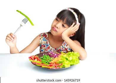 Little asian girl with expression of disgust against broccoli, Isolated over white