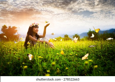 Little asian girl in garden with hands up and butterflies