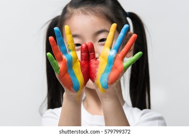 Little Asian girl with hands painted in colorful paints