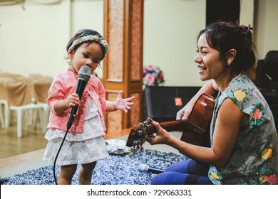 Little Asian girl happy to sing with her mom