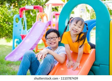 Little asian girl and her brother playing at school playground