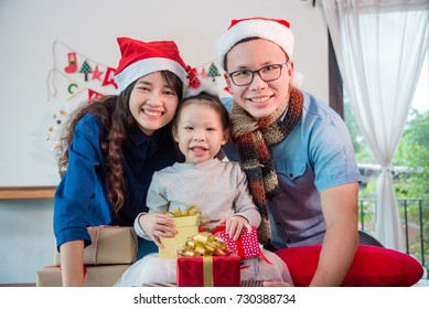 Little asian girl and her parents with christmas gift boxes smiling at  camera bb6a83368