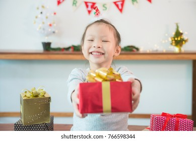 Little asian girl holding Christmas gift box with smiles at home