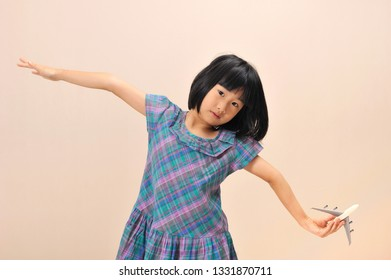Little asian girl holding model airplane and try to fly like an airplane.