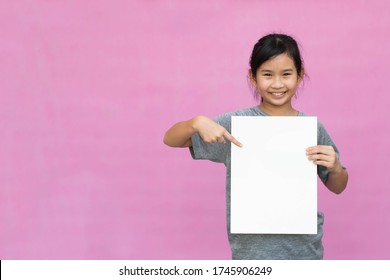Little asian girl holding white paper isolated on pink background.