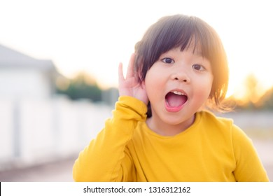 Little asian girl holds her hand near her ear and listening something.Exciting face on funny child girl wear yellow shirt in winter time and listening to curious good news.