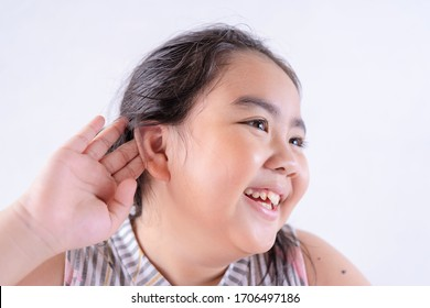 Little asian girl holds her hand near her ear and listening something. Exciting face on funny, She is sitting in her house.
