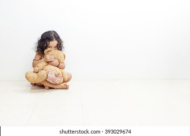Little Asian girl Hug teddy bear, her Eyesight filled with terror.