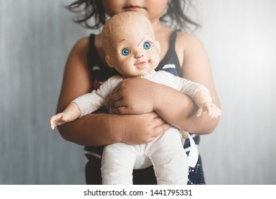 little asian girl hugging her favorite worn grimy doll. Concept of Lonely child, love, childhood and parenting. Selective focus on the doll.