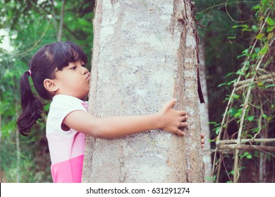 Little Asian girl hugs and kisses a tree.Wild love concept