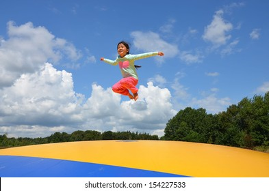 Little Asian girl jumping in the air