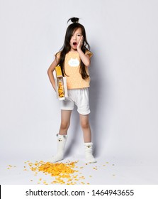 Little asian girl kid in home clothes is worried about her failure with corn flakes. She spilled it out on the floor during breakfast. She moans and yawns on gray background