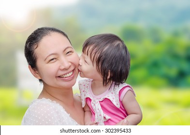 Little Asian girl kissing her mom in garden