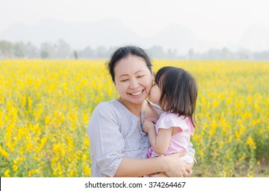 Little Asian girl kissing her mom in flower field