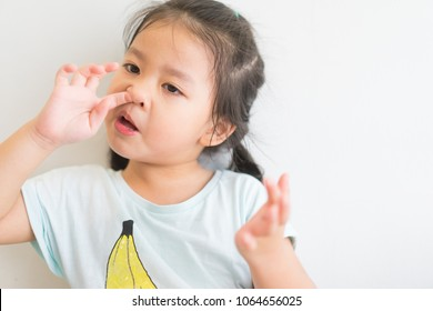 Little asian girl like picking a snot and eat snot and play snot in living room at home.