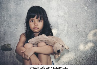 Little asian girl long black hair sad and crying in the wall with doll. kid lonely. kidnappad indoors. Domestic violence concept.
