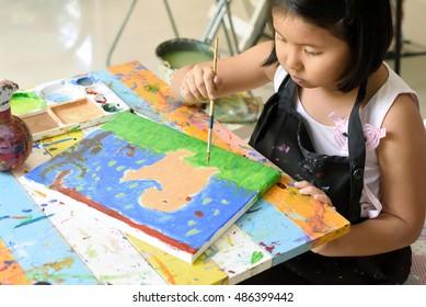 Klein asiatisches Mädchen liebt es, Hunde auf Leinwand mit Acryl-Farbe in Kunstschulen zu malen, Kinderkunst