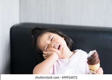 Little asian girl with a oral toothache and hands holding ice cream cone.Child girl touching her cheek and feel aching bad tooth.Pain in the human body.Concept for dentist, diseases,tooth day.